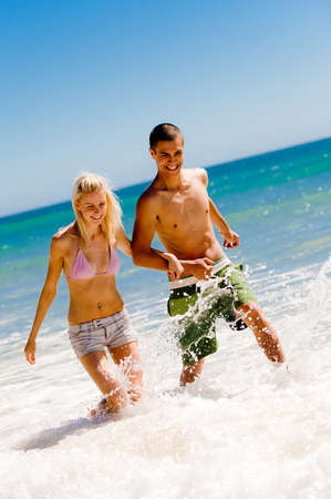 A young couple walking through the waves photo