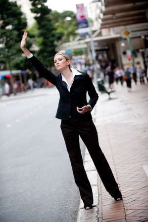 hail: A young professional woman trying to hail a cab in the city Stock Photo