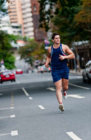 A good-looking man is out running in the city photo