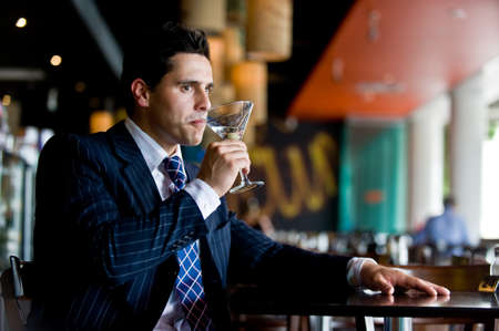 sophisticated: A young businessman sitting in a bar with a martini