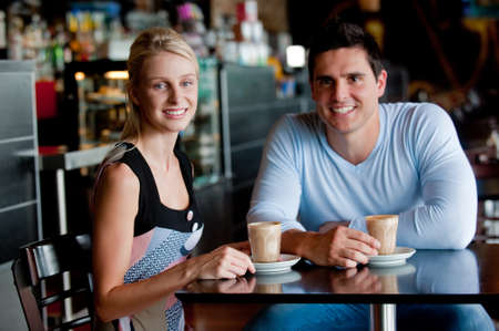 A young attractive couple sitting together in a cafe with coffee
