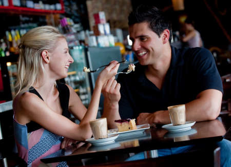 A young attractive couple sitting together in a cafe with coffee ad cake