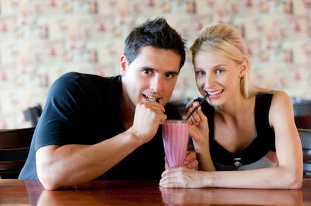 A young man and woman sharing a pilk milkshake Stock Photo - 4168863