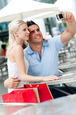 A young attractive couple on vacation taking their photo on a digital camera photo
