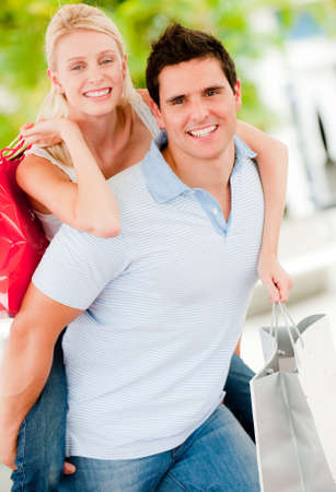 A young attractive couple together outside with shopping bags photo