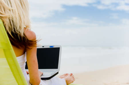 A young woman sitting on the beach with laptop computer
