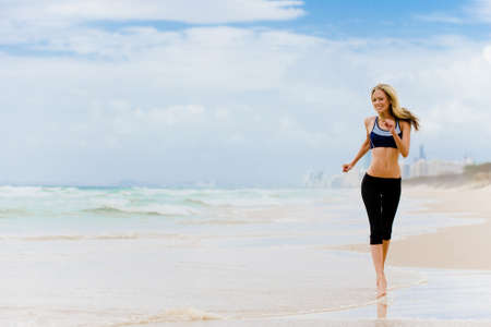 surfers paradise: A young woman with running along Surfers Paradise beach in Australia Stock Photo