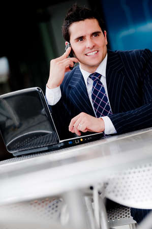 Businessman sitting with laptop and phone