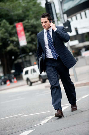 Businessman on phone crossing the street Stock Photo