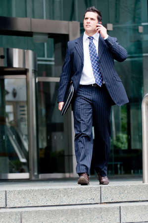 Businessman on phone coming out of a building