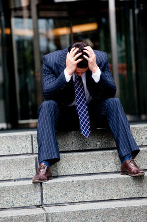 distraught: Distraught businessman sitting outside with head in hands