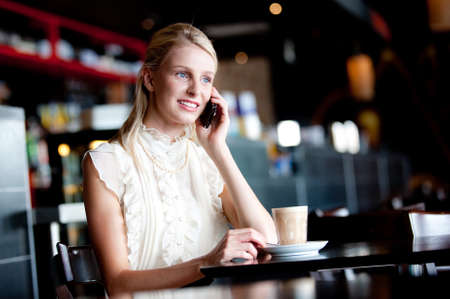 Woman having coffee and talking on the phone Stock Photo