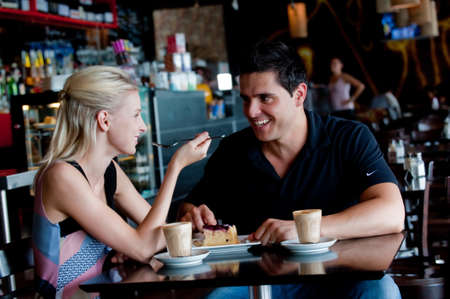 A young attractive couple sitting together in a cafe with coffee and cake