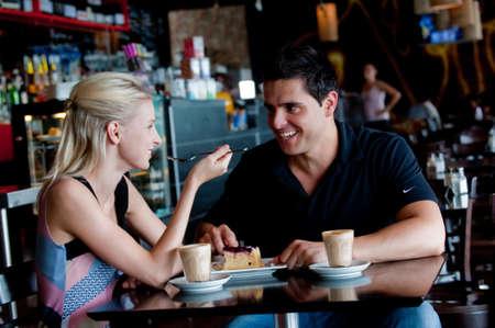 cafe bar: Een jong paar aantrekkelijke zitten samen in een cafe met koffie en gebak
