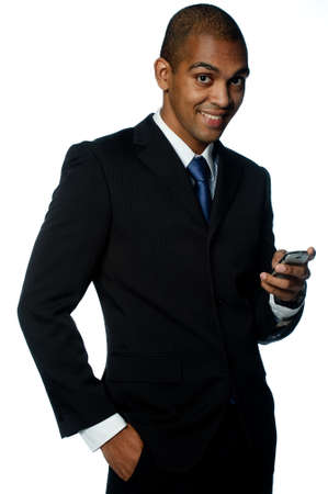 A confident young black businessman with mobile phone on white background