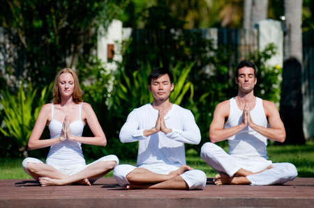 Three young adults in white meditating in ygoa pose outside in tropical setting Stock Photo - 4643558
