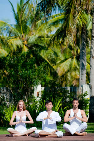 Three young adults in white meditating in ygoa pose outside in tropical setting photo