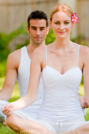 A couple sitting outside in a tropical setting doing yoga looking relaxed