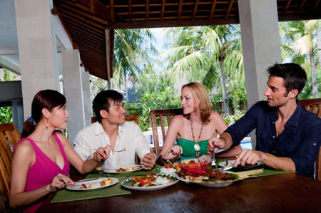 sharing food: A group of four adults enjoying lunch at their villa on vacation