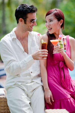 An attractive couple having drinks by the pool on vacation photo