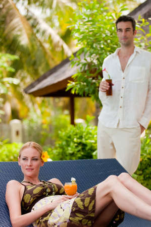 An attractive couple having drinks on vacation Stock Photo - 4643609