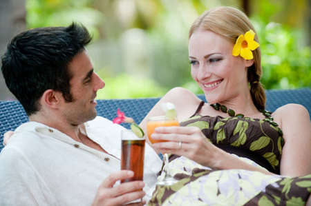 An attractive couple having drinks outside on vacation photo