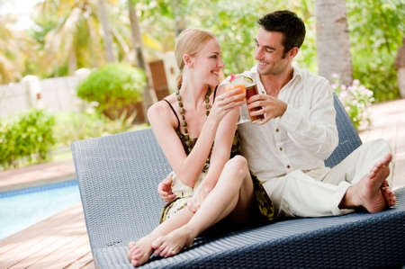 An attractive couple having drinks ouside on vacation photo