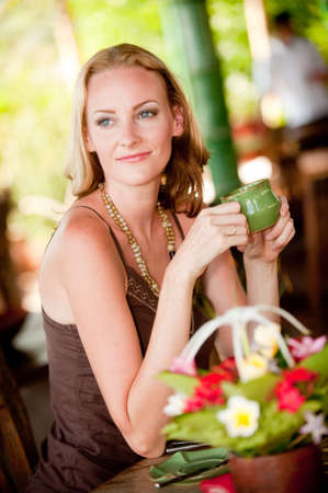 A beautiful woman drinking tea at a restaurant in tropical resort Stock Photo