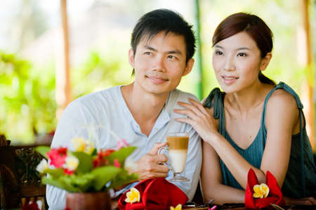 A young couple enjoying morning coffee whilst on vacation photo