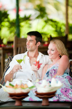 A young couple enjoying cocktails before lunch whilst on vacation Stock Photo