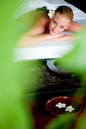 An attractive woman relaxing with hot stones on back before massage photo