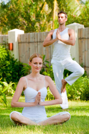A couple practising yoga outside in the garden photo