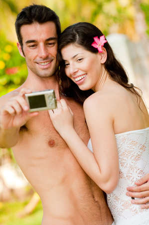 A young couple on vacation taking their photograph outside in tropical setting photo
