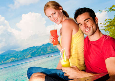 A young couple on vacation enjoying drinks with a sea view photo