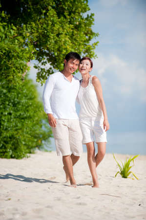 An attractive couple walking together on the beach Stock Photo