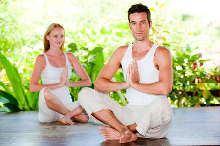An attractive couple doing yoga together