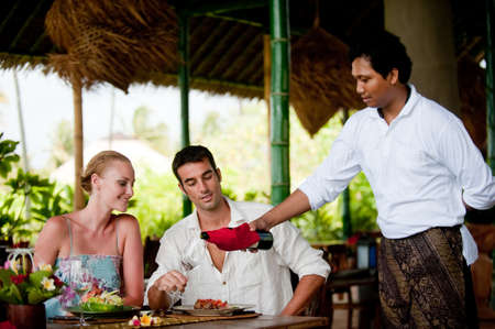 A waiter pours wine for a couple having dinner at a resort restaurant on vacation photo