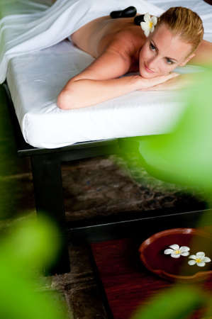 hot rock therapy: An attractive woman relaxing with hot stones on back before massage Stock Photo