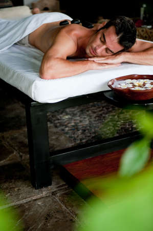 A good-looking man relaxing with hot stones on back before massage photo