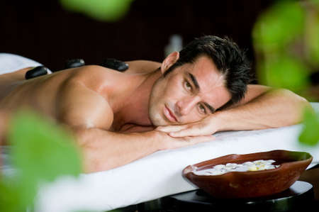 hot rock therapy: A good-looking man relaxing with hot stones on back before massage