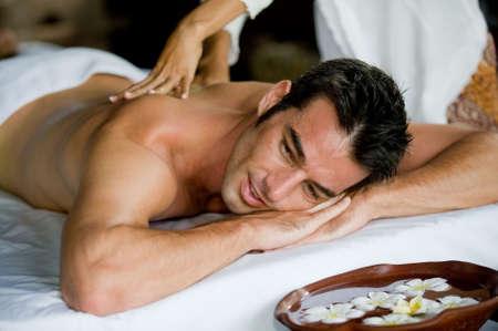 mimos: Un hombre bien parecido conseguir un masaje de espalda acostado