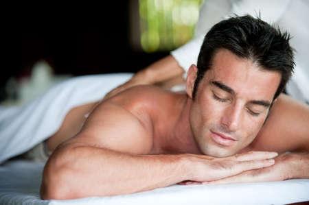 masajes relajacion: Un hombre bien parecido conseguir un masaje de espalda acostado