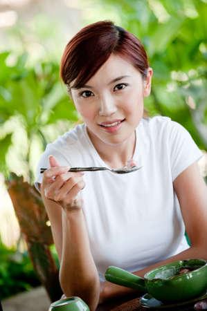mujer china: Una joven atractiva mujer china de comer frutas y yogur para el desayuno en un resort tropical Foto de archivo