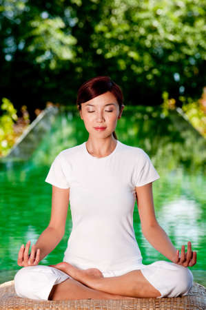 A beautiful Chinese woman sitting in a yoga pose outside photo