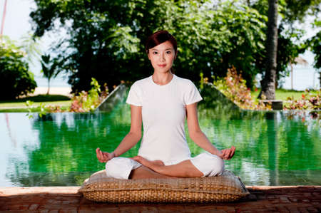 A beautiful Chinese woman sitting in a yoga pose outside Stock Photo