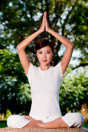 A beautiful Chinese woman sitting in a yoga pose outside Stock Photo - 4801271