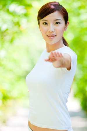 An attractive Chinese woman in white standing in a natural setting photo