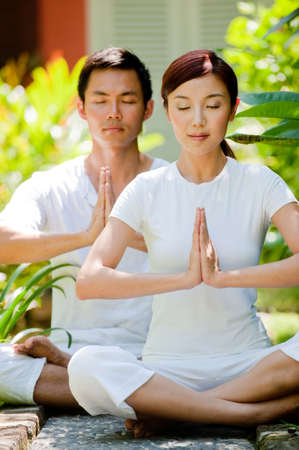 A young attractive Chinese couple meditating outside in natural environment
