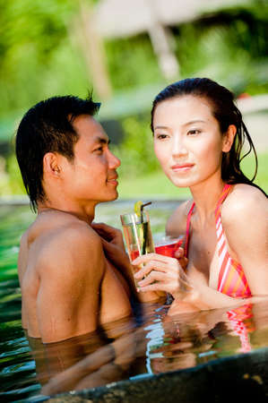An attractive Chinese woman and man in swimming pool with cocktails Stock Photo - 4801293