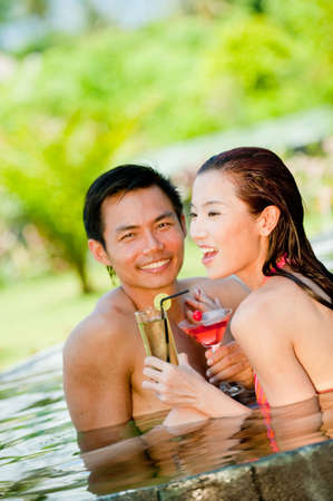 An attractive Chinese woman and man in swimming pool with cocktails